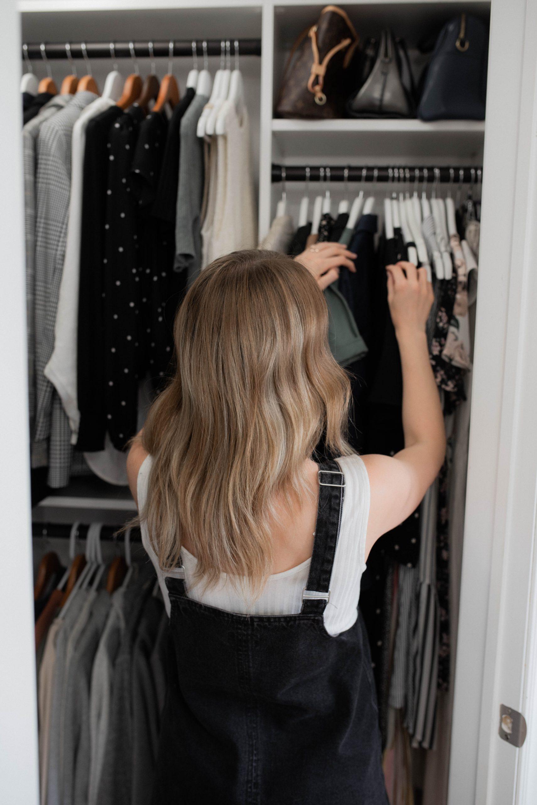 woman looking through minimized wardrobe