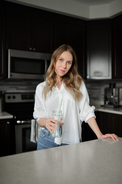 Woman standing in kitchen with glass of water